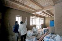Pohled na rozpracovaný trámový strop a stěnu z nepálených cihel s jílovou omítkou. Na stropě je vidět rozvod elektřiny ve stíněných kabelech, které snižují elektrosmog v domě.