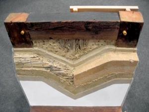 Příklad zateplení hrázděného zdiva. V levé části obrázku je zateplení provedeno 5 cm silnou rákosovou deskou. V pravé části 5 cm silnou hobrou. Na povrchu je jílová omítka s jutou natřená kasionovým mlékem.