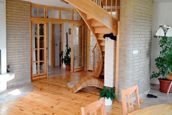 Točité schodiště podél akumulační stěny z nepálených cihel v nízkoenergetickém rodinném domku.