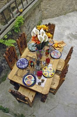 Ručně vyřezávaný stůl smotivem Alcatraz, materiál mexická borovice. Cena  89000Kč. Na stole tradiční mexická pestrá keramika