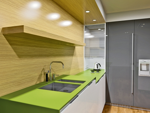 Dřez ve zvýšené úrovni 90cm šetří záda při mytí nádobí. Obložení stěny je vdezénu běleného dubu.