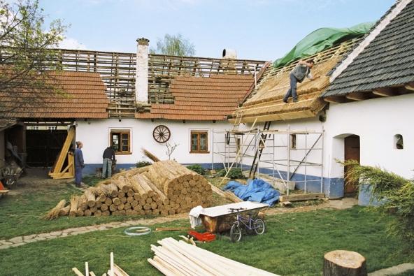 Takto vypadá pošívání střechy rákosovými došky v praxi – dole je připravený materiál.