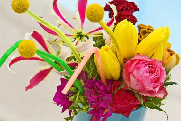 Ve vtipném aranžmá, které připomíná sladký koktejl, jsou na barevná brčka napíchané ozdoby zkvětů kraspédií. Pěknou podívanou dotvářejí nevadlce, gloriózy, frézie, růže atulipány.