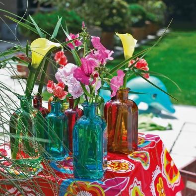 """Fialovo-bílá prázdninová pohoda skopretinami (Leucanthemum) arozrazilem (Veronica)  2 l Vůni exotiky navodí výrazné aneobvyklé strelície soranžovomodrými květy. Do talíře vám tak budou sympaticky hledět """"ptáci"""" sdlouhým zeleným zobákem avýrazným vztyčeným chocholem oranžových amodrých pírek. Doplní je drobnokvěté zelenožluté chryzantémy  3 l Dopřejte si něžné tóny. Stačí postavit na stůl mísu seustomami  4 l Sbírku lahví na pestrém ubruse zastiňuje zářivé avzdušné aranžmá shrachorem, kalami, pivoňkami aslézovcem (Lavatera)."""