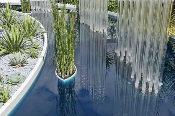 """Průzračnou vodu doplňují průhledné sloupky, působící  jako sloupce vody, a""""loďka""""s bambusy."""