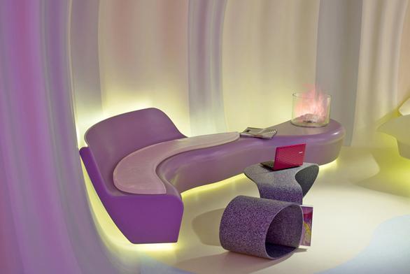 """Sedačka """"ā la Karim"""" na pozadí zakřivených stěnových panelů. Povrch sedací plochy tvoří měkká vrstva ze silikonu."""