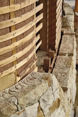 Obvodová stěna s provětrávanou vzduchovou mezerou: zprava podezdívka z pískovce, vzduchová mezera, dřevěné bednění a protivětrová zábrana z juty.  Za ní bude izolační prostor vyplněný balíky slámy.
