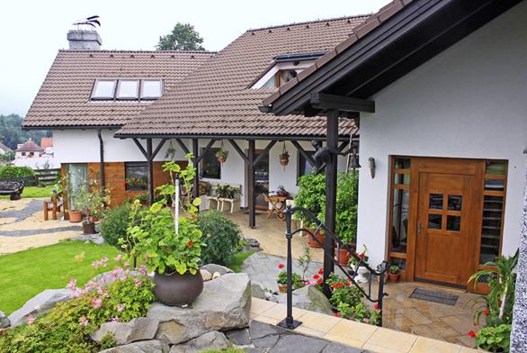 Dvougenerační rodinný dům vJablonném vPodještědí je obklopen trávníkovou plochou aokrasnými záhony. Hlavní vchod otevírá pohled dozahrady, vchody do domu jsou součástí celkové koncepce řešení více než půlhektarového pozemku.