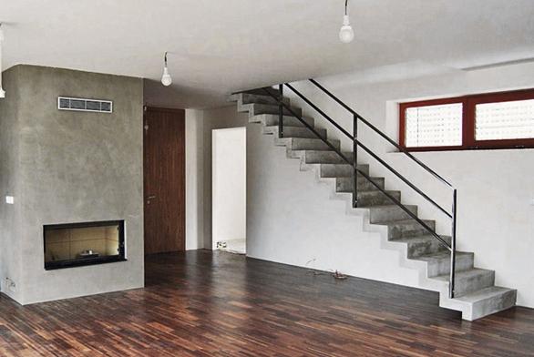 Volný prostor obývacího pokoje doplňuje jednoduchý tvar přímého ramene. Náročná lomenicová konstrukce je konzolovitě kotvená do obvodového zdiva. To vše navíc sjednocuje stěrka na povrchu schodiště akrbovém tělese. Čistý prostor zvýrazňují bílé plochy stěn astropu sjednotným odstínem dveří apodlahy. Názorná ukázka toho, jak lze ijednoduché schodiště zajímavě avkusně začlenit do interiéru celého domu.