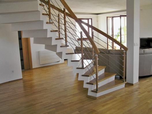 Že schodištím sluší volný prostor, jednoduchost, zajímavá konstrukce atvar, ukazuje tato realizace. Lomenicová konstrukce spodkosenou podstupnicí otloušťce 100mm je obložena spárovkou pouze na stupnicích. Kontrast dřevěného stupně sbílými plochami schodiště odlehčuje.