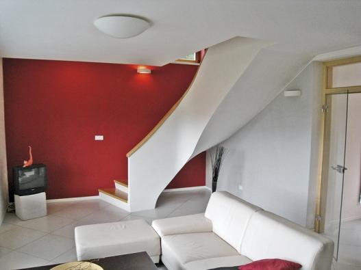 Inspiraci varchitektuře 30. let hledali istavitelé tohoto schodiště. Jednoduchý půdorysný tvar do L připomíná dnes již klasické schodiště předválečné kavárny ERA vBrně. Toto schodiště bylo zdispozičních důvodů umístěno do kouta obývacího pokoje. Zábradí je vytvořeno pomocí subtilní betonové moniérky zakončené lepeným dřevěným madlem. Pro zvýraznění elegantních křivek schodiště byla štítová stěna vymalována sytou červenou barvou.