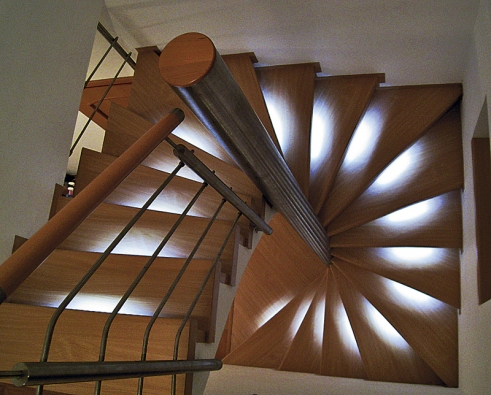 Ani minimalistický prostor cca 2 x 2m nemusí bránit tomu, aby se zde zrealizovalo kvalitní, bezpečné, pohodlné apěkné schodiště. Toto betonové je obloženo schodišťovým stupněm z postformingu. Pod přesahující hranou jsou uloženy LED diody, které osvětlují nášlapnou plochu spodního stupně. Za tmy pak vznikají zajímavé obrazce. Stupně lemuje jemný soklík. V tomto případě je obložena také podstupnice.