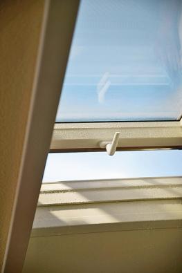 """Výklopné plastové střešní okno skličkou ztvrzeného plastu nastavené do  polohy """"otevřeno"""" (Roto)."""