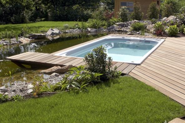Koupel ve Swim Spa, zapuštěné do terasy, ozvláštní těsné sousedství zahradního jezírka.
