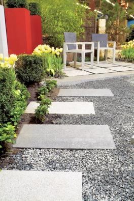 Betonové dlaždice použité jako šlapáky mezi zelení akameny (ZAHRADA PRAHA).