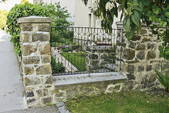 Obvodová zeď kolem vilky je do ulice na několika místech otevřená kovanými mřížemi. Soukromí obyvatel zajišťuje zelená clona.