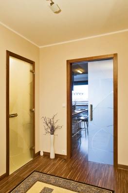 Kombinace celoskleněných dveří Stylus votočném aposuvném provedení do stavebního pouzdra sobložkovou dýhovanou zárubní, sklo satináto bronz (VV SKLO).