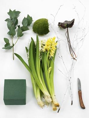 Připravte si žlutý abílý hyacint, listy Eucalyptus robusta aGalax urceolata, mech, obarvené březové větvičky apěnovou aranžovací hmotu.