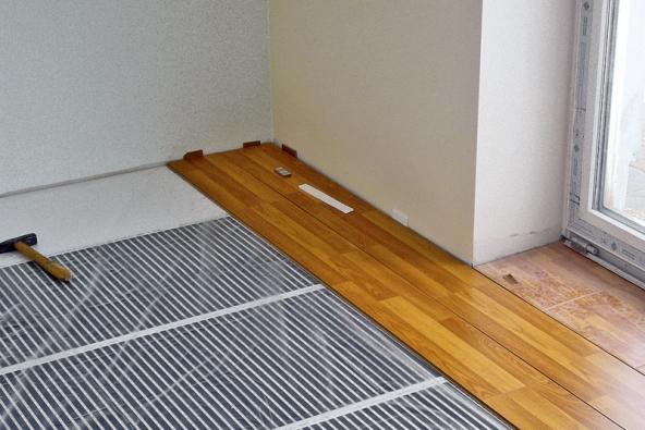 Pokládka laminátové podlahy na topnou fólii Ecofilm je díky malé tloušťce fólie snadná anevyžaduje žádné dodatečné stavební úpravy (např. urekonstrukcí).