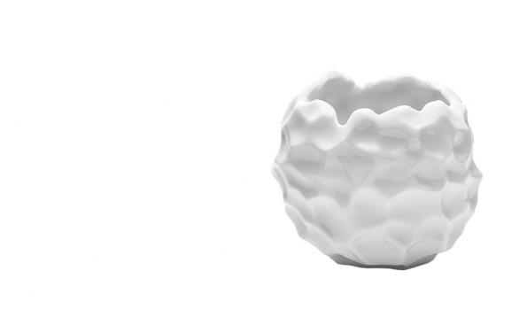 Svícen z bílého porcelánu na čajovou svíčku je protipólem uhlazených a esteticky vytříbených kousků. Celý nepravidelný povrch je posetý otisky prstů, bezprostředně působí také nestejně tvarovaný lem. Romantické světlo tak dodá přirozenou atmosféru  a láká dotknout se zajímavého povrchu (NORMANN COPENHAGEN, Dánsko).