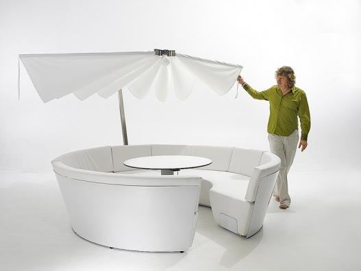 Zahradní nábytek Cosmos se slunečníkem tvoří dvě polokruhové sedačky pro devítičlennou společnost. Kruhový stolek lze snížit na úroveň sezení, čímž se vytvoří plocha pro odpočinek až 7 lidí. Polštáře jsou vyrobeny zmateriálů, vhodných pro venkovní použití. Útulné soukromí vytvoří nízko položený slunečník (také tmavě šedý nebo černý) snápaditým otevíracím azavíracím mechanismem. Magnety na obou koncích udrží slunečník otevřený. Když je příliš větrno, magnety se rozpojí aslunečník se sám automaticky složí. Materiál odolává špíně avětru (EXTREMIS, Belgie).