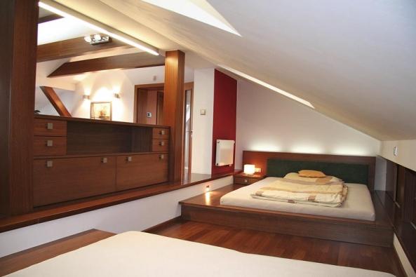 Zajímavé dělení podkrovní místnosti na ložnici aobytnou část soriginálním řešením vstupu do postele (ALNUS).