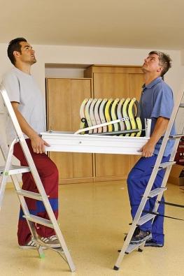Dvě osoby vyzvednou schodiště do stavebního otvoru atřetí pomocník je již připraven vhorním půdním prostoru aupevní rám schodiště pomocí čtyř kusů nosníků.