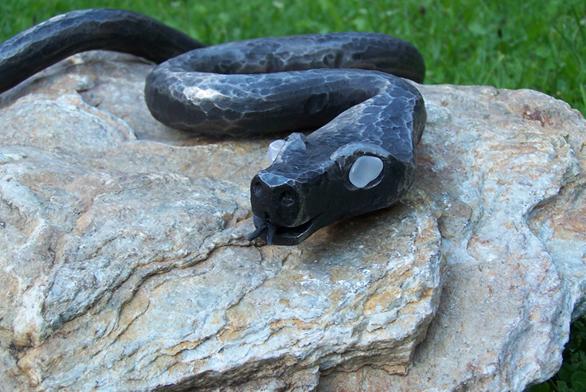Plastika Polední siesta – had je zjednoho kusu, oči růženín, povrch je leštěný aantikorozně ošetřený (OKRASNÉ KAMENY).