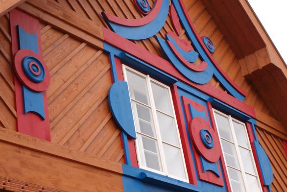 Detail fasády jednoho z Gočárových domů, kde se nachází restaurace s venkovním posezením.