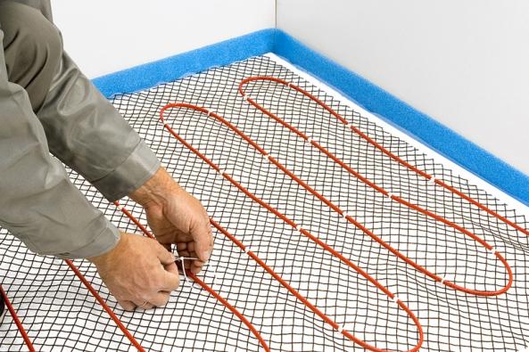 1) Instalace kabelu: Před začátkem pokládky topení je nutné změřit plochu vytápěné podlahy apodle Příručky pro podlahové topení určit optimální množství topného kabelu. Kabel přichytíme ke kovové instalační síti pomocí kabelových spon KBL-10 vpožadované rozteči. Výhodou sítě je snadné vyměření rozteče azároveň zpevnění následné krycí betonové (anhydritové) vrstvy.