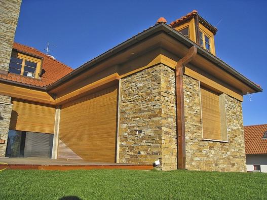 Dům stíněný předokenními venkovními roletami. Přehřívání interiéru brání iobvodové zdivo zkamene (případně obklad odvětrané fasády) azvětšený přesah střechy.