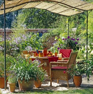 Středomořské rostliny vkvětináčích, proutěný zahradní nábytek apergola promění hodiny na zahradě vmalou dovolenou.