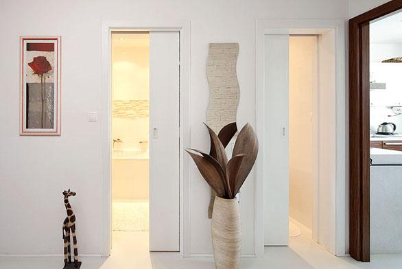 Dveře, které se zasouvají do stavebního pouzdra, mají nulovou náročnost na prostor – pro klasické dveře by bylo rozbití vázy dílem okamžiku (J.A.P.).