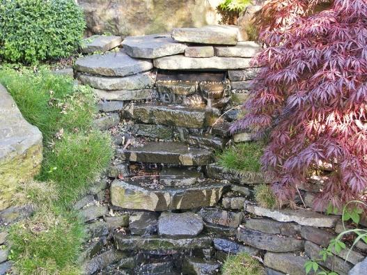 Stačí stisknout vypínač vgaráži ado jezírka začne proudit voda. Kameny avodní hladinu doplňuje krásně zbarvený  javor dlanitolistý  (Acer palmatum).