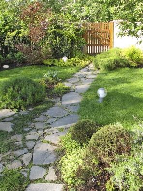 Dlažba zčedičových kamenů prochází od garáže vřesovištěm kbočním vrátkům. Vnoci zahrada ožije ve světle zahradních lamp.