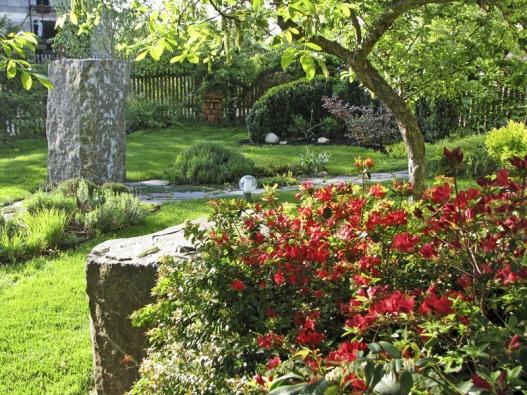 Vpřední části zahrady vyniká jako dokonalý solitér jeden zčedičových sloupků. Na jaře vystřídají květy meruňky výrazně barevné azalky.