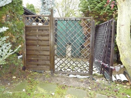 Venkovní jednotky čerpadla umístěné na zahradě jsou umně skryty za dřevěnou zástěnou.