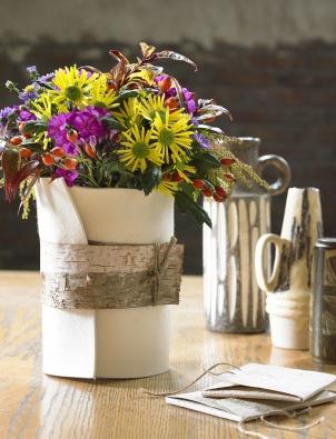 Zobyčejné vázy uděláte neobyčejnou, když ji obalíte plstí abřezovou kůrou. Pestrobarevnou nostalgickou kytici tvoří plamenka achryzantéma. Kromě nich jsou použité astry, leukotoe, šípek apieris.