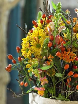Pestrému aranžmá posloužila jako váza ekologická papírová taška. Velmi přirozenou podzimní kytici tvoří chryzantéma, mečík, klejicha, třezalka splody, hledík ašípek.