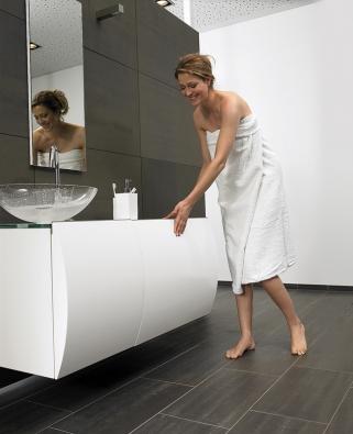 Stačí poklep na čelní plochu aby hluboká zásuvka koupelnové skříňky se systémem Touch Latch Senso® vyjela azpřístupnila iobsah další uvnitř skryté zásuvky (foto GRASS).