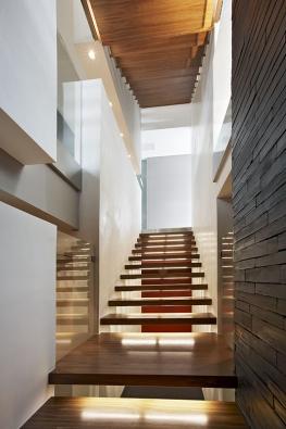 Masivní dřevěné desky, kotvené pomocí ocelových prvků dobočních stěn, umožňují dennímu světlu proniknout až dosuterénu domu. Elegantní řešení zateliéru Design by Donlić.