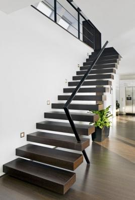 Jednotlivé schodišťové stupně jsou pomocí nosných ocelových prvků konzol kotveny donosné schodišťové stěny alemovány jednoduchým ocelovým zábradlím. Zajímavý prostorový efekt zvýrazňuje tmavá dýha wengé.