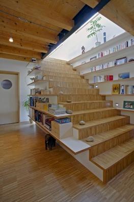 Architekt Tomáš Klanc navrhl doobývacího pokoje vdřevostavbě atypickou sestavu knihovny aschodiště zlaminovaných adřevěných desek. Jsou kotveny pomocí ocelových trnů přímo donosné konstrukce stěny.