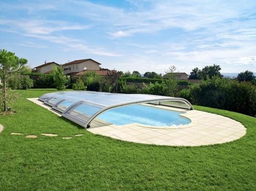Teleskopické bezkolejnicové zastřešení Desjoyaux umožňuje využití celého odkrytého bazénu vsezoně. Je diskrétní, estetické – začlení se dokrajiny apřizpůsobí se iarchitektuře (DESJOYAUX).