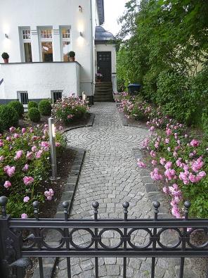 Jednoduchá aelegantní kompozice přístupové cesty lemované růžovými záhony vjednom barevném tónu (Home & Garden).
