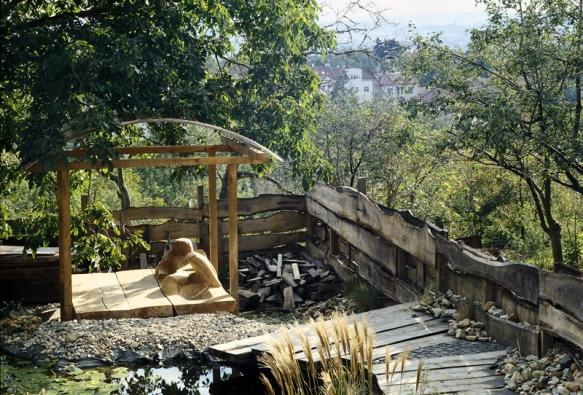 Ve spodní části zahrady je umístěn jednoduchý altánek sdřevěnou plastikou. Vzniklo zde jakési klidné útočiště, vhodné třeba pro popíjení  čaje, tolik oblíbené mezi Japonci.