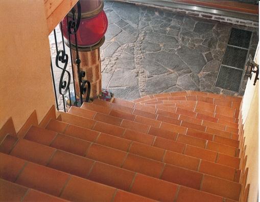 Hrubá dlažba zlomového kamene doplněná žulovými kostkami se výborně doplňuje se schody obloženými keramikou (Ceram object).