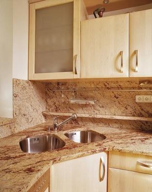 Obložení doplněné poličkou apracovní deska kuchyňské linky zleštěné žuly (Granit Holec).