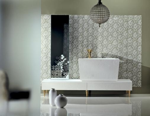 Bohatě vzorované obklady akombinace několika typů, dekor na umyvadle, zlatá armatura azdobně tvarované nožky nábytku – itak může vypadat koupelna, jak ji představuje značka Tosco Quatro.