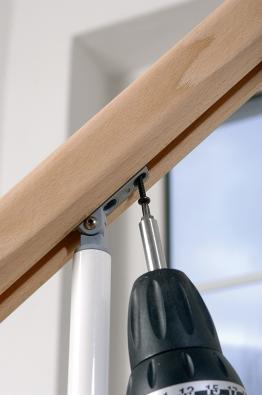 Dokončení montáže schodiště Arké spočívá vpřišroubování madla khorním úchytkám nasloupcích. Aku šroubovák usnadní práci (J.A.P.).